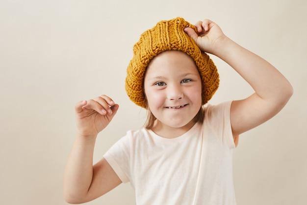 Portret van een klein meisje met het syndroom van down die wollen hoed dragen en bij camera glimlachen die op witte achtergrond wordt geïsoleerd