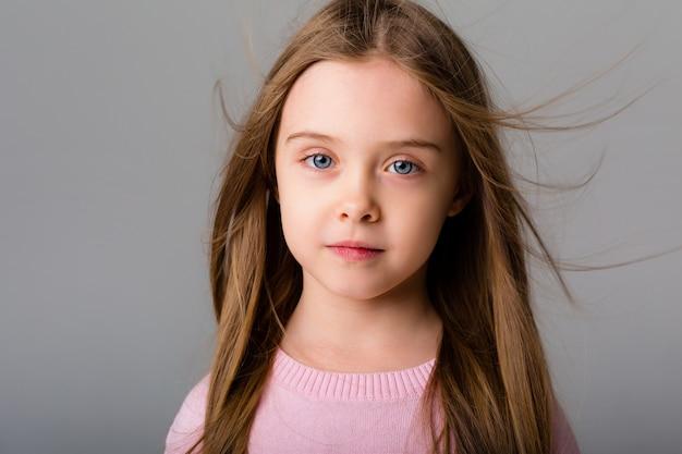 Portret van een klein meisje met lang haar op een lichte ruimte