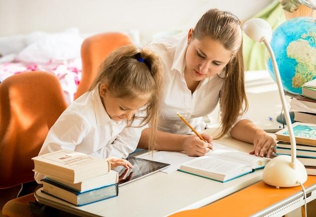 Portret van een klein meisje met moeder die op tablet kijkt hoe ze huiswerk moet maken