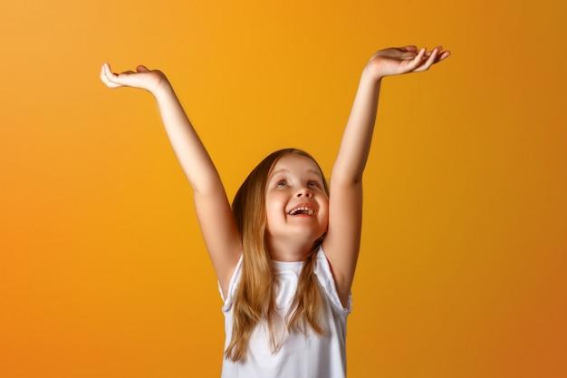 Portret van een klein meisje met opgeheven armen.