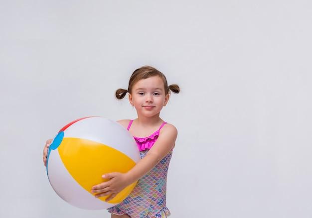 Portret van een klein meisje met paardestaarten in een zwempak met een opblaasbare bal op een geïsoleerd wit