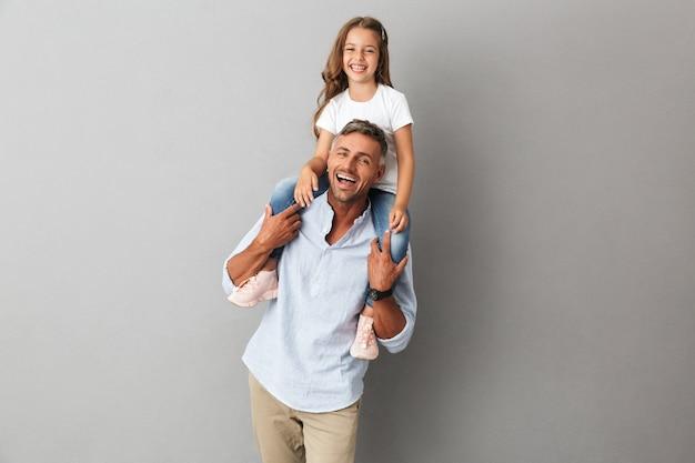 Portret van een klein meisje met plezier en zittend op de nek van haar gelukkige vader, geïsoleerd over grijs