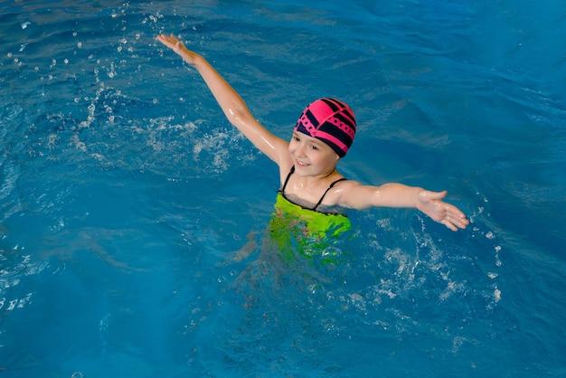 Portret van een klein meisje met plezier in het binnenzwembad