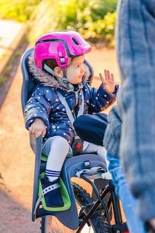 Portret van een klein meisje met veiligheidshelm op het hoofd zittend in een fietsstoeltje achter haar vader. veilig en kinderbeschermingsconcept.