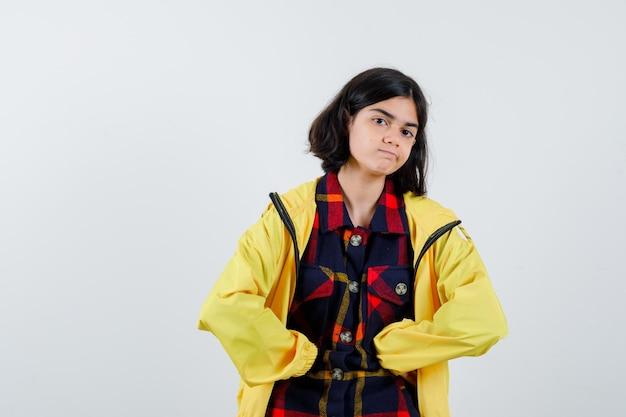 Portret van een klein meisje met vuisten op de buik in een geruit overhemd, jasje en zelfverzekerd vooraanzicht