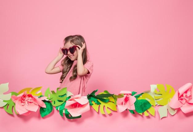 Portret van een klein meisje met zonnebril op een roze achtergrond