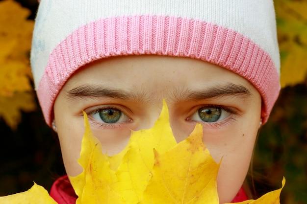 Portret van een klein meisje, ogen zijn close-up, die gele herfstbladeren in haar handen houdt. klein kind wandeling in herfst park. het concept van weersverandering, herfst komt eraan, omgekeerde school.