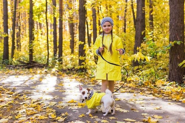 Portret van een klein meisje op een achtergrond van oranje en gele bladeren in een zonnige herfstdag