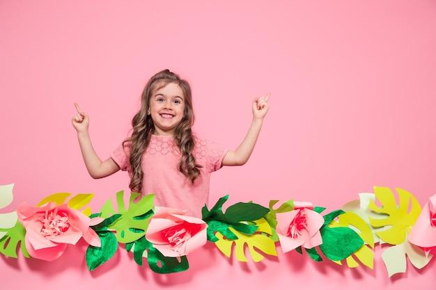 Portret van een klein meisje op een zomer roze achtergrond met papieren bloemen, plaats voor tekst, zomer reclame concept