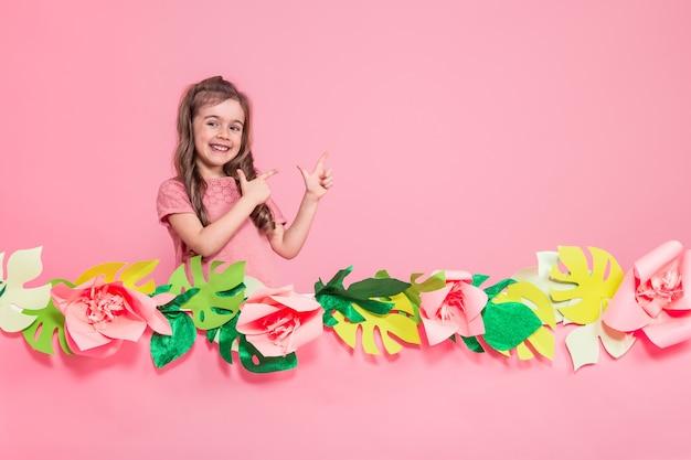 Portret van een klein meisje op een zomer roze achtergrond