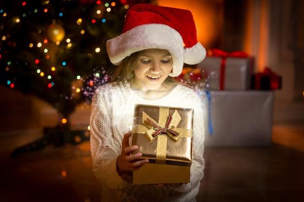 Portret van een klein meisje poseren met gloeiende gouden geschenkdoos