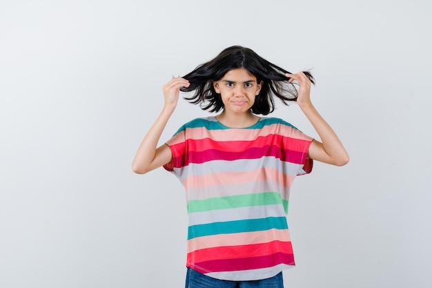 Portret van een klein meisje poserend met vliegend haar in t-shirt en ziet er prachtig uit vooraanzicht