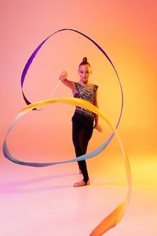 Portret van een klein meisje, ritmische gymnastiekkunstenaarsopleiding geïsoleerd op gekleurd