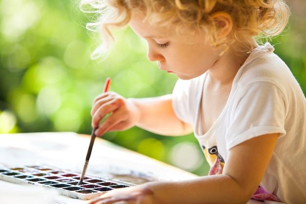 Portret van een klein meisje schilderen, zomer buiten