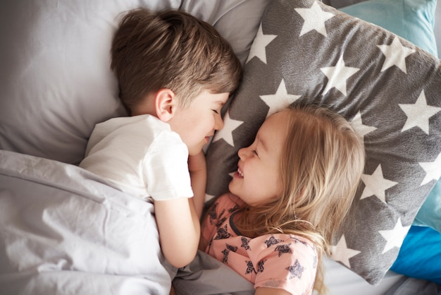 Portret van een klein meisje slapen naast haar broer close-up