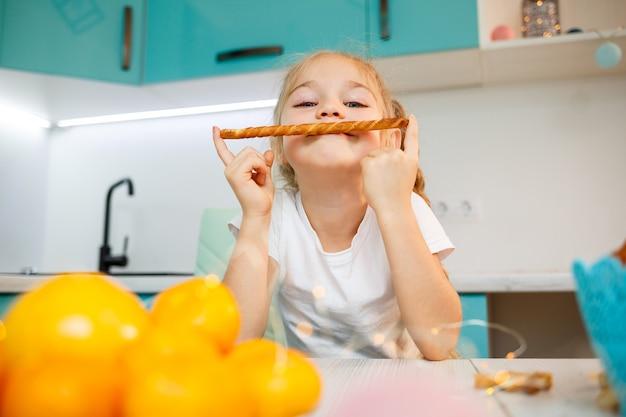Portret van een klein meisje van 7 jaar oud zit in de keuken en speelt met broodstengels. kind ontbijt in de keuken