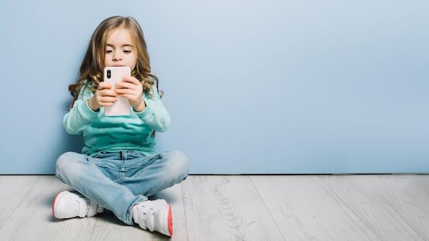 Portret van een klein meisje, zittend op een hardhouten vloer kijken naar smartphone