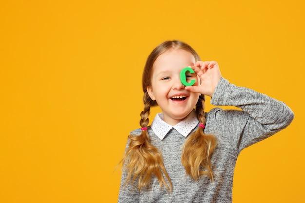 Portret van een klein meisjeskind. schoolmeisje houdt de letter c.