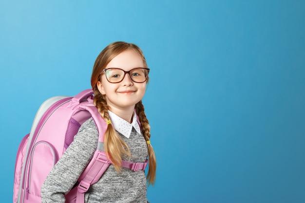 Portret van een klein meisjesschoolmeisje met een rugzak op een blauwe achtergrond