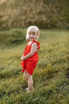 Portret van een klein mooi meisje in een rode jurk op aard op zomerdag vakantie
