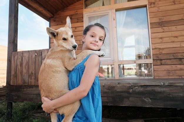 Portret van een klein mooi meisje in jurk met haar hond op haar handen en buitenshuis kijken