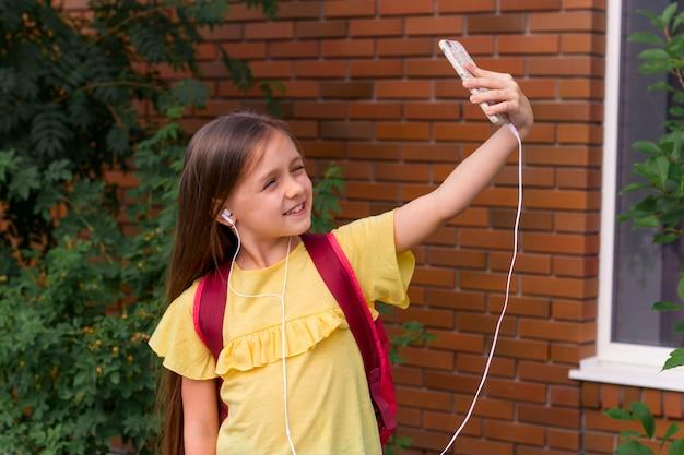 Portret van een klein mooi meisje met behulp van een mobiele telefoon en het nemen van een selfie