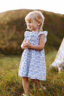 Portret van een klein mooi meisje op de natuur op zomerdag vakantie.