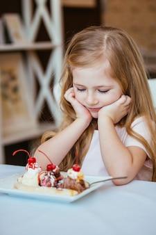 Portret van een klein mooi meisje, zittend in een café aan de tafel te denken met een bolletje ijs met fruit. gelukkig kind