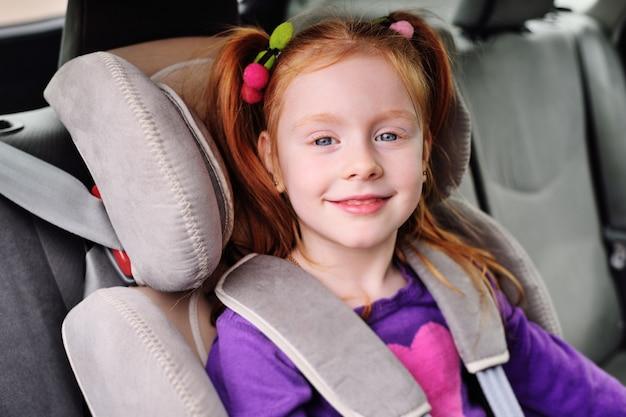 Portret van een klein roodharig meisje in de auto