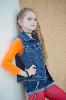 Portret van een klein roodharig meisje met lichte make-up in een denimvest.
