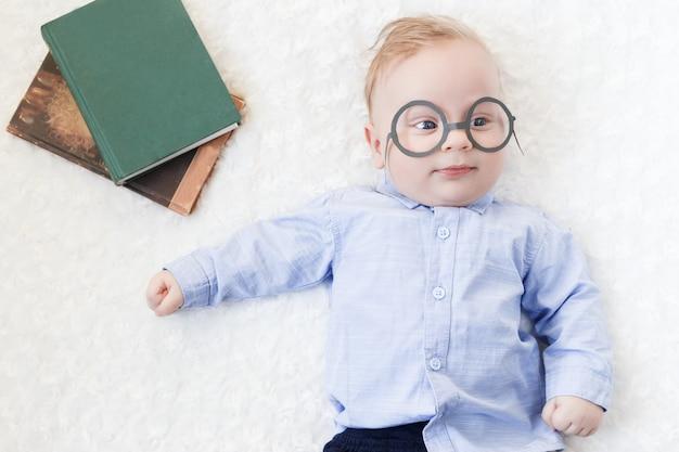 Portret van een klein schattig kind in een shirt en glazen met boeken liggend op het bed