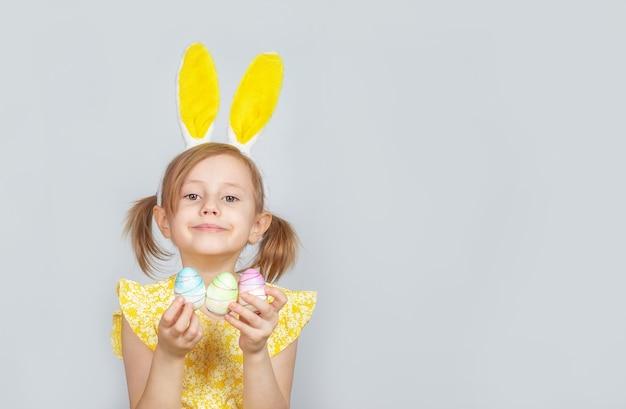 Portret van een klein schattig lachend meisje met konijnenoren en versieringen voor pasen in handen op een grijs oppervlak