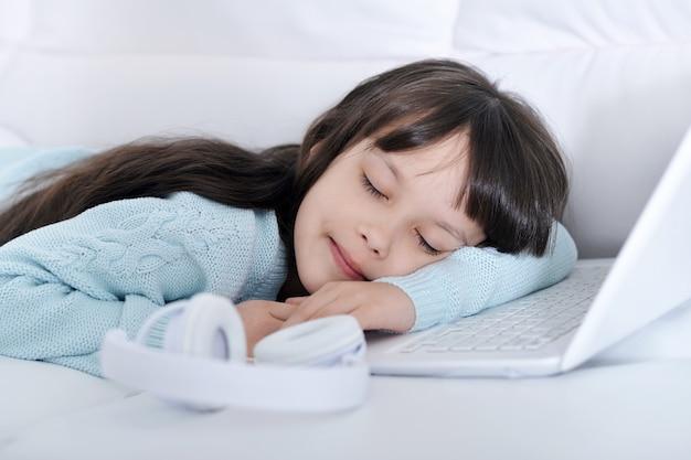 Portret van een klein schattig meisje dat in de buurt van laptop slaapt