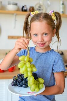 Portret van een klein schattig meisje in de keuken met boodschappen en gezonde voeding