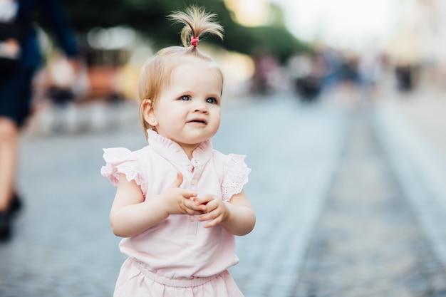 Portret van een klein, schattig, mooi meisje loopt door de stad in een roze jurk.