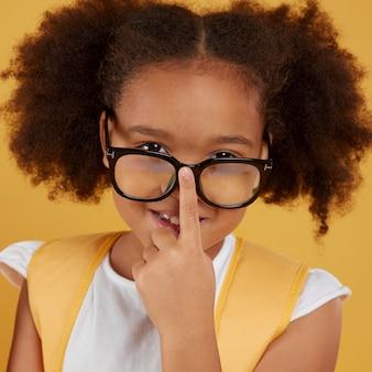 Portret van een klein schoolmeisje dat een bril draagt