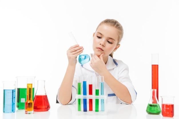 Portret van een klein schoolmeisje in een witte laboratoriumjas die chemische experimenten maakt met veelkleurige vloeistof in reageerbuizen geïsoleerd over een witte muur