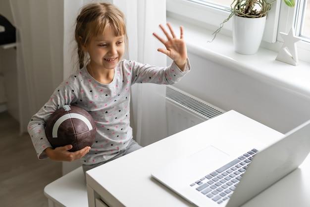 Portret van een klein sportief meisje met rugbybal die naar laptop kijkt