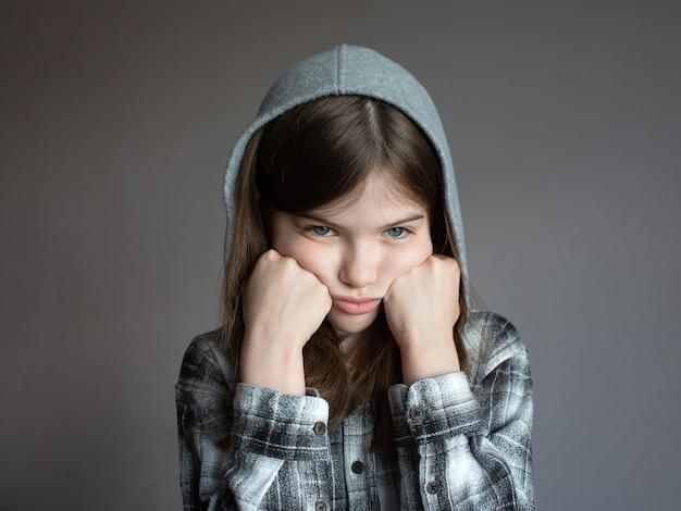 Portret van een klein verdrietig meisje in een hoodie op donker