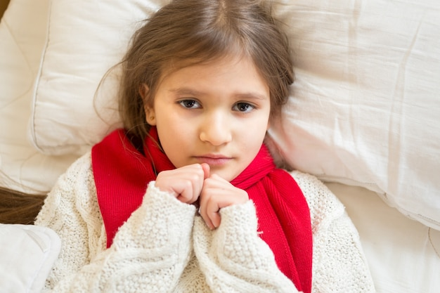Portret van een klein verdrietig meisje in een witte trui die onder de deken op bed ligt