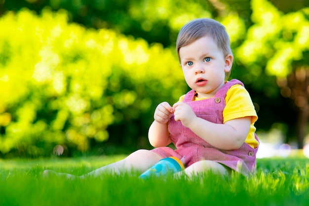 Portret van een klein verrast meisje, een peinzend kind zit in het park op het gras buiten