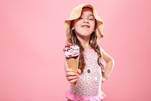Portret van een klein vrolijk meisje met ijs op een gekleurde muur