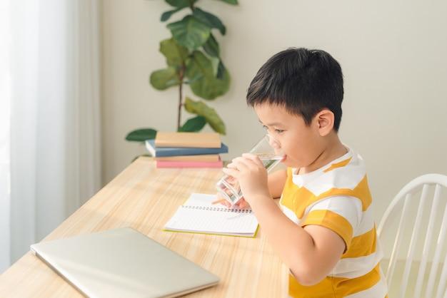 Portret van een kleine aziatische jongen die water drinkt terwijl hij een laptop gebruikt, aan een bureau zit en huiswerk maakt. e-learning en onderwijsconcept.