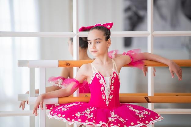Portret van een kleine ballerina in een heldere karmozijnrode tutu die zich bij de machine voor een spiegel bevindt
