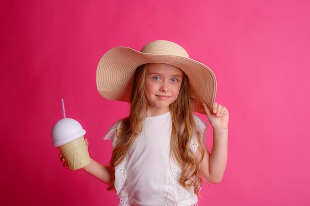Portret van een kleine blonde in een hoed met een blikje verkoelende cocktail.