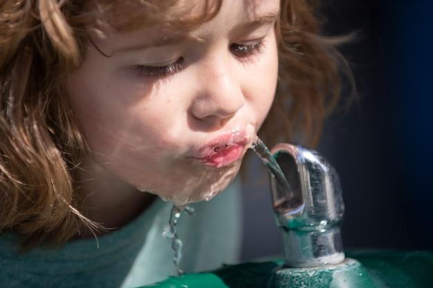 Portret van een kleine blonde jongen drinkwater buiten in het park, close-up. schattige kinderen gezicht. positief emotioneel kind. dorstige kinderen.