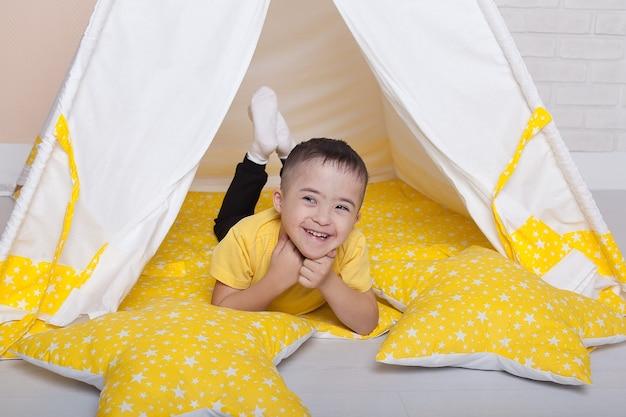 Portret van een kleine gehandicapte jongen down die in de speelkamer zit en glimlacht.