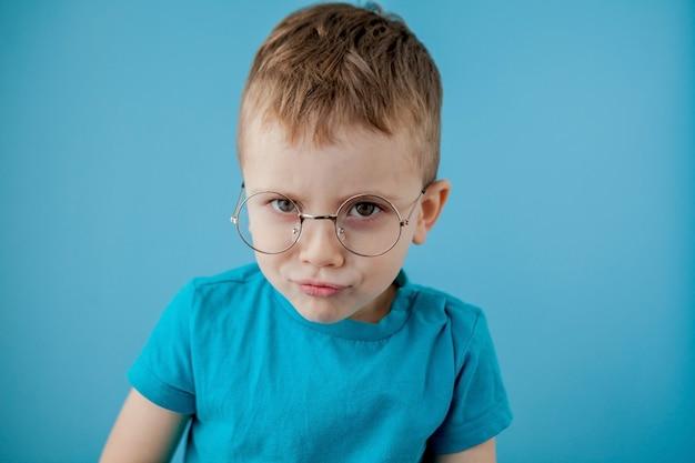 Portret van een kleine glimlachende jongen in grappige glazen. school. peuter. mode