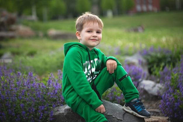 Portret van een kleine glimlachende jongen op de achtergrond van een bloeiend park