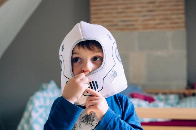 Portret van een kleine jongen die een kostuum van de astronautenhelm draagt